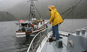 Missionary in rain gear on bow deck of Coastal Messenger.